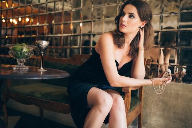 黒のベルベットのドレス、イブニングドレス、リッチでスタイリッシュな女性、エレガントなファッショントレンド、デートを待っている、小さな金色のハンドバッグを手に持ってヴィンテージカフェに座っているエレガントな美しい女性