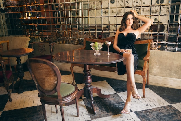 Elegant beautiful woman sitting in vintage cafe in black velvet dress, evening gown, rich stylish lady, elegant fashion trend, sexy seductive look, attractive skinny figure