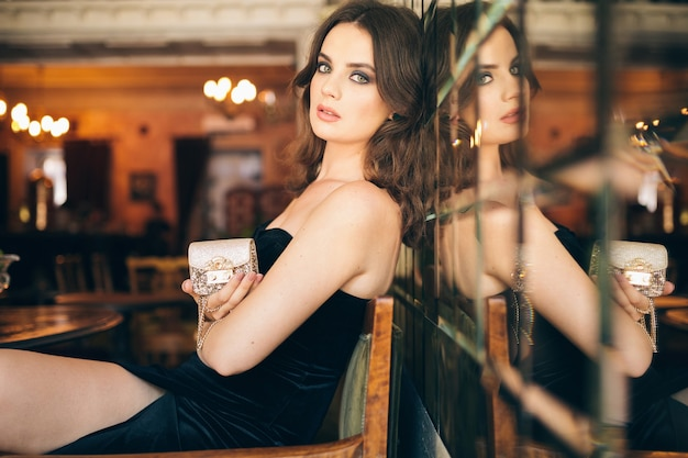 Elegant beautiful woman sitting in vintage cafe in black velvet dress, evening gown, rich stylish lady, elegant fashion trend, waiting on a date, holding little golden handbag in hand