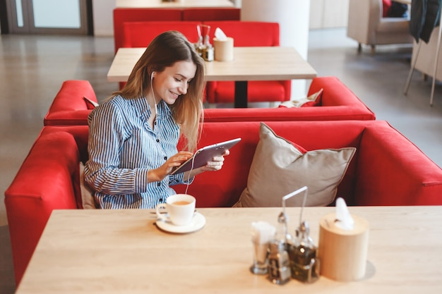 Elegant beautiful woman with tablet computer drinking tea at cafe