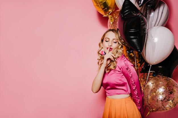 Donna elegante compleanno in posa sulla parete rosa