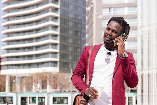 도시를 걷는 우아한 흑인 사업가가 손에 커피를 들고 전화 통화를 하고 있다