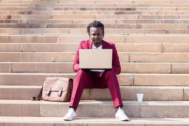 우아한 흑인 사업가는 도시, 기술, 원격 작업 개념의 계단에 앉아 노트북을 가지고 일합니다.