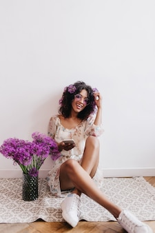 Elegant black girl expressing happiness during indoor photoshoot with flowers. portrait of happy african lady sitting on the floor with bouquet and phone.