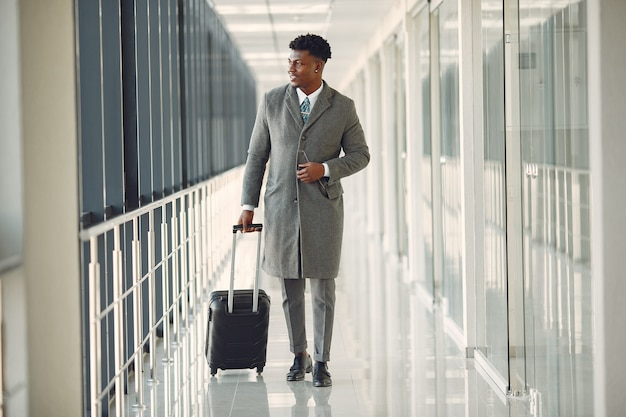Elegant black man at the airport with a suitcase