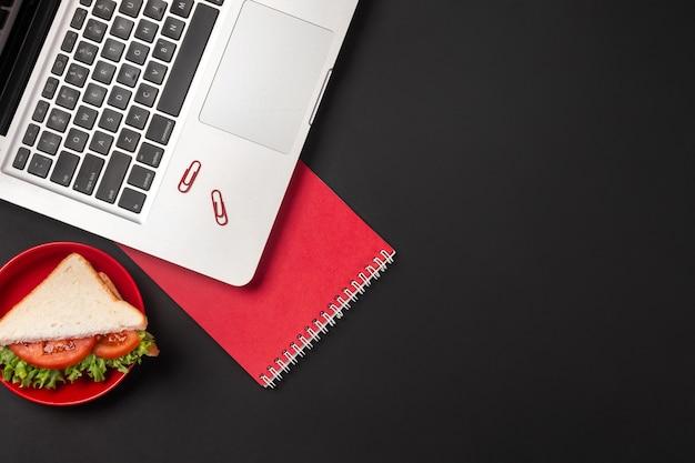 Элегантный черный рабочий стол офиса с ноутбуком и бутербродом на обед. вид сверху с копией пространства.