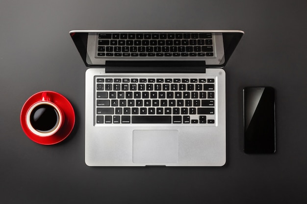 Elegant black office desktop with laptop, cup of coffee and mobile phone. top view.