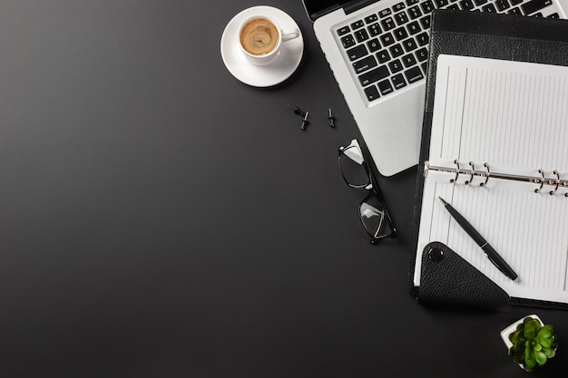 Elegant black office desktop with laptop and cup of coffee. top view.