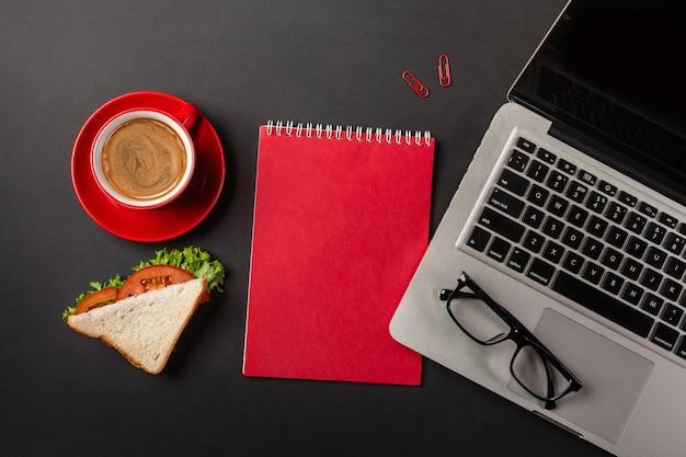 Элегантный черный рабочий стол офиса с ноутбуком, чашкой кофе и бутербродом на обед. вид сверху с копией пространства.