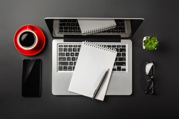 Elegant black office desktop with laptop, notebook, red cup of coffee and mobile phone. top view.