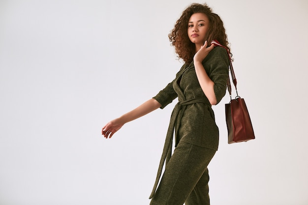 Elegant black woman with curly hair in fashionable green suit