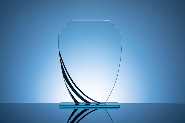 Elegant blank glass shield trophy on blue gradient