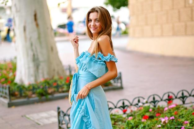 Elegante donna felice beata che cammina per strada europea, indossando un abito blu elegante femminile e una borsa di paglia