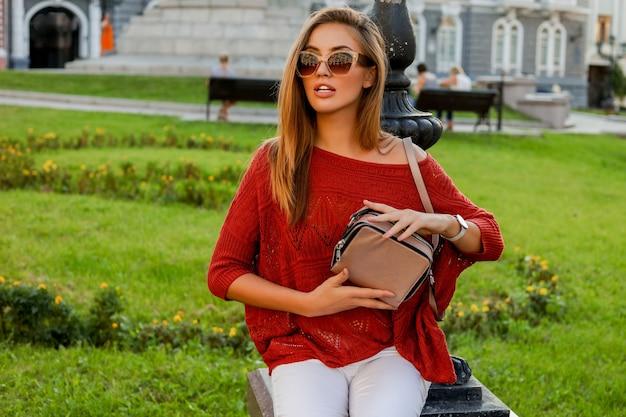 Elegante donna bionda in autunno alla moda ourfit in posa sulla strada. indossare occhiali da sole, maglione e jeans bianchi.