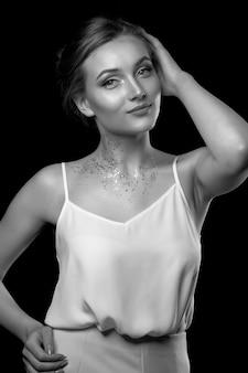 エレガントな金髪の女性は、スタジオで影にポーズをとって白いシルクのドレスを着ています。黒と白のショット
