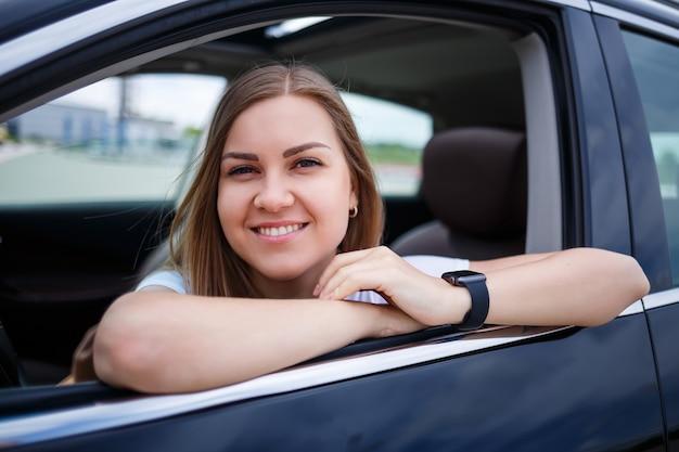 Элегантная белокурая красивая женщина, сидящая в роскошном автомобиле. девушка стильная и много зарабатывает. независимая женщина бизнесмен концепция
