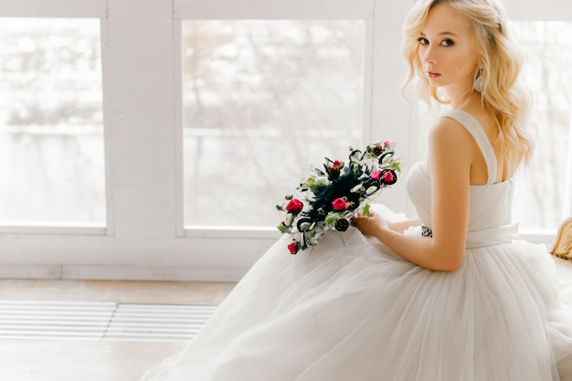Elegant blonde bride in beautiful wedding dress with boquet of decorative flowers bright studio portrait.