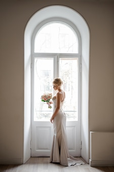 Elegant blonde bride in a lovely white dress holding a wedding bouquet