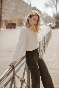 Elegant blonde curly woman in stylish velvet brown pants and trendy white blouse looks down and leans on fence on city street