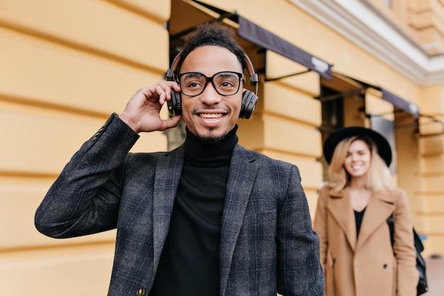 아프리카 남자 웃음 뒤에 서있는 베이지 색 복장에 우아한 금발 소녀. 거리에서 편안한 헤드폰에 놀란 흑인 남자의 야외 사진.