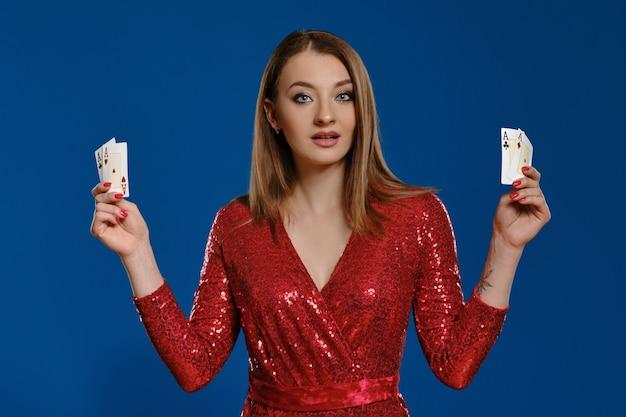 Элегантная блондинка с макияжем, татуированной рукой, в красном платье с пайетками показывает четыре туза, удивленно выглядя, позируя на синем фоне. азартные развлечения, покер, казино. крупный план.