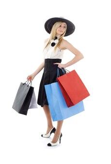 ショッピングバッグとレトロな帽子のエレガントなブロンド