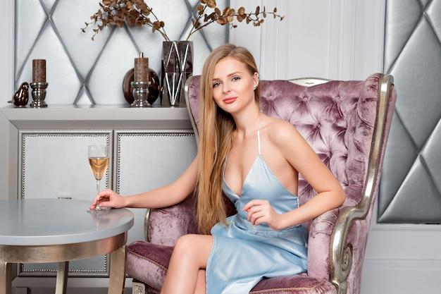 레스토랑에서 와인의 유리를 가진 우아한 금발 아가씨. 긴 머리 완벽한 몸과 고급스러운 인테리어에 알코올을 마시는 파란 이브닝 드레스를 입고 예쁜 얼굴 화장 아름 다운 섹시 한 젊은 여자.