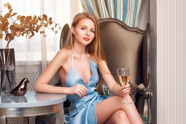 レストランでワインのグラスとエレガントなブロンドの女性。長い髪の完璧なボディと豪華なインテリアでアルコールを飲んで青いイブニングドレスを着てきれいな顔のメイクの美しいセクシーな若い女性。