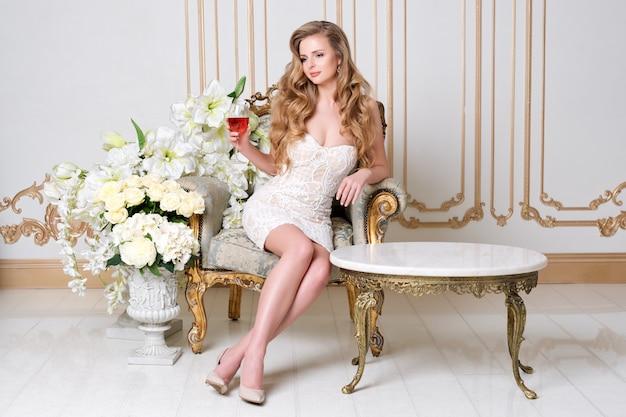 레스토랑에서 와인의 유리를 가진 우아한 금발 아가씨. 긴 머리 완벽한 몸과 가벼운 고급스러운 인테리어에 알코올을 마시는 이브닝 드레스를 입고 예쁜 얼굴 화장 아름 다운 섹시 한 젊은 여자.