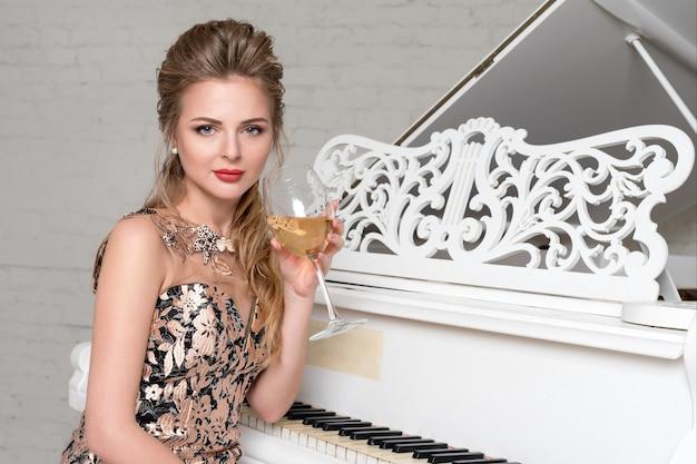 豪華なクラシックなインテリアの白いグランドピアノの近くに座っているワインのグラスを持つエレガントなブロンドの女性。完璧なボディときれいな顔のメイクアップを祝う、アルコールを飲むイブニングドレスの若い女性