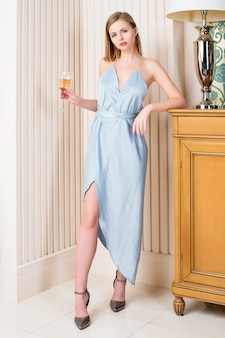 Elegant blonde lady with glass of wine in restaurant. beautiful sexy young woman with long hair perfect body and pretty face make-up wearing blue evening dress drinking alcohol in luxury interior.