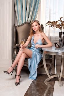 Elegant blonde lady with glass of wine in restaurant
