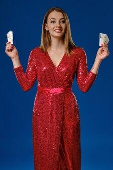 赤いスパンコールのドレスを着た、化粧、入れ墨の手を持つエレガントなブロンドの女性は、青い背景に対してポーズをとって、4枚のトランプを見せて笑っています。ギャンブルの娯楽、ポーカー、カジノ。閉じる。