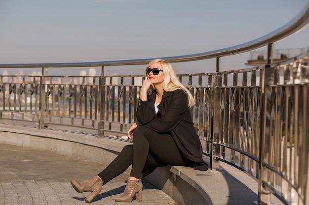 검은 코트를 입고 포즈를 취한 우아한 금발 모델, 도시 배경에 선글라스를 끼고