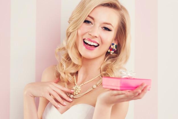 Elegante donna bionda che tiene un regalo rosa