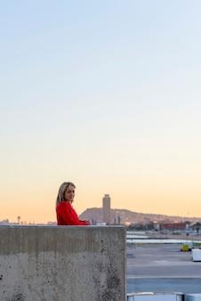 Элегантная белокурая женщина, опираясь на стену во время отдыха на фоне городского пейзажа
