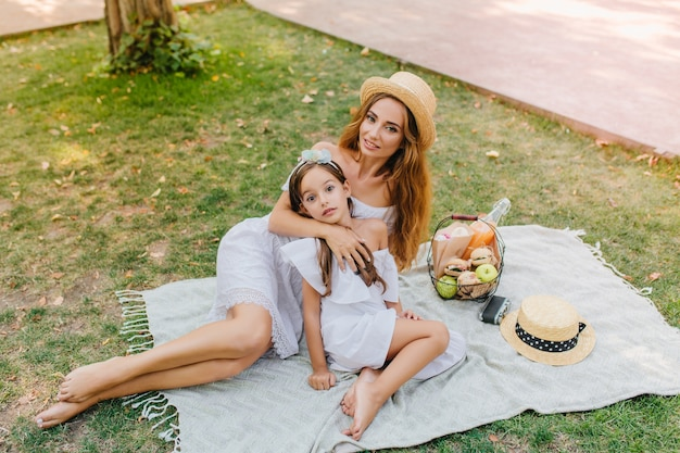 エレガントな金髪の女性は週末にリンゴのバスケットと白い毛布の上に横たわっています。公園で天気の良い日を楽しんでいる陽気な女の子と彼女の母親の屋外の肖像画。