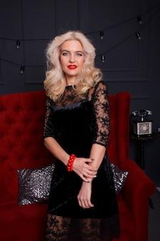 赤い肘掛け椅子でエレガントな金髪の女性の肖像画