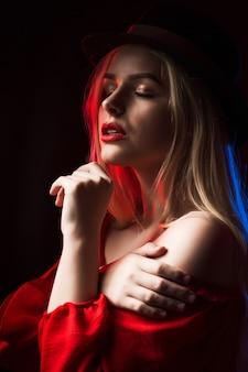 青と赤の光で影の中でポーズをとって赤いブラウスと帽子を身に着けているエレガントなブロンドの女性