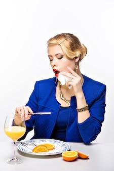 Элегантная белокурая женщина с причёской смотрит на отражение ножа