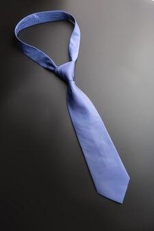 黒の背景にエレガントな青いネクタイ