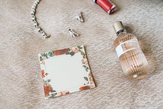 Elegant bottle of perfume on the armchair with a pink necklace of the bride