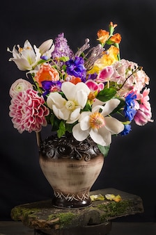 Elegant bouquet of flowers in a vase on a black space in dark style, floral still life
