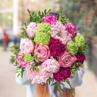 An elegant bouquet of pink and purple flowers with decorative green leaves