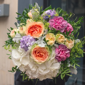 An elegant bouquet of white, orange, yellow and purple flowers with decorative green leaves