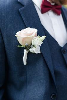 グレーのジャケットに柔らかいピンクのバラが付いたエレガントなブートニエール