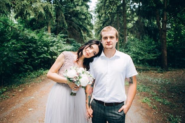 結婚式の日に屋外で一緒にポーズをとるエレガントな新郎新婦