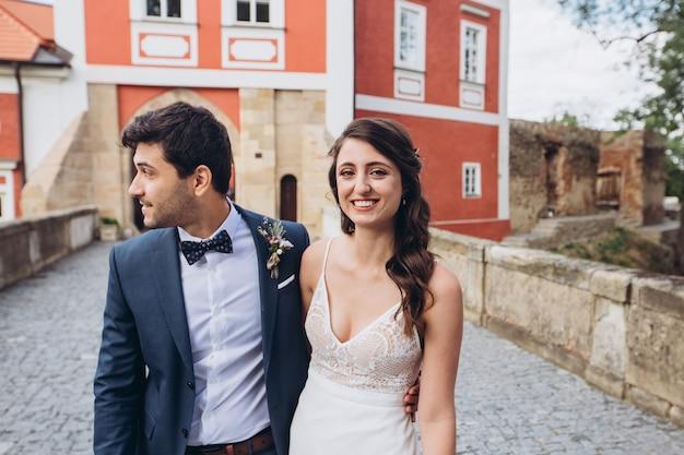 Элегантные жених и невеста позирует вместе на открытом воздухе