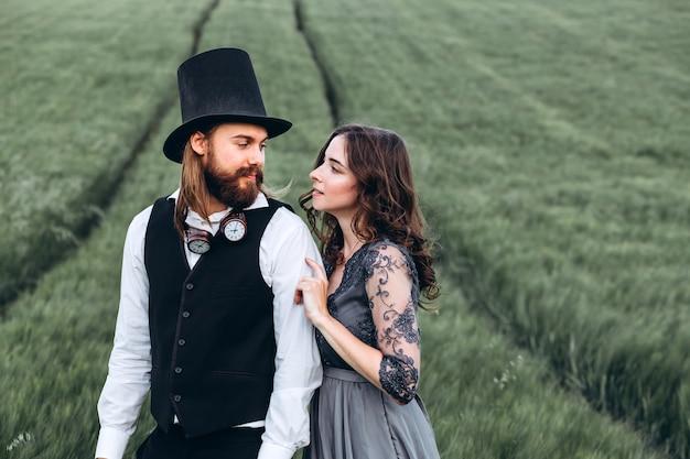 Элегантная невеста и жених гуляют и позируют на зеленом поле