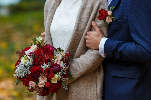 Elegant bride in dress with lace holding bridal bouquet of flowers in pink and green colors. and groom in dark blue suit with boutonniere